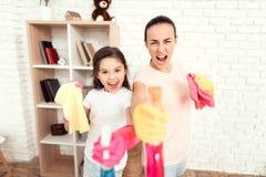 Mutter und Tochter werfen zu Hause mit Ausrüstung für das Säubern auf Lizenzfreies Stockfoto