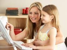 Mutter und Tochter zu Hause unter Verwendung des Computers Stockbilder