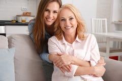 Mutter und Tochter zusammen weekend zu Hause das Umarmen, Kamera schauend Lizenzfreie Stockfotos
