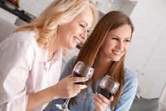 Mutter und Tochter zusammen weekend zu Hause den trinkenden Rotwein, der heraus das Fenster schaut Stockfotografie