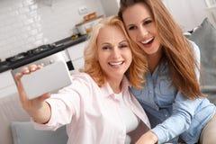 Mutter und Tochter zusammen weekend zu Hause, selfie Fotos machend Stockfotos