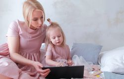 Mutter- und Tochterblick in der Tablette Junge attraktive blonde Frau mit ihrer kleinen reizend Tochter im Rosa kleidet das Aufpa Lizenzfreie Stockbilder
