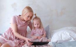 Mutter- und Tochterblick in der Tablette Junge attraktive blonde Frau mit ihrer kleinen reizend Tochter im Rosa kleidet das Aufpa Stockfoto