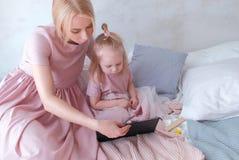 Mutter- und Tochterblick in der Tablette Junge attraktive blonde Frau mit ihrer kleinen reizend Tochter im Rosa kleidet das Aufpa Stockfotos