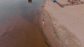 Mutter- und Tochterlauf entlang dem Fluss entlang dem Sand Strand Sonniger Sommertag Lufttrieb stock video footage