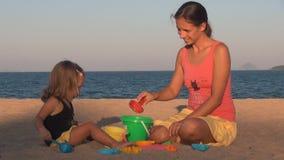 Mutter- und Tochterspielen sie klopfen auf dem Schaufeleimer und -lachen stock video
