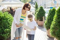 Mutter- und Tochtertourist, der die Karte auf der Straße der europäischen Stadt betrachtet Stockfotografie