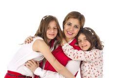 Mutter und Umarmen mit zwei Töchtern Lizenzfreies Stockbild