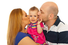 Mutter und Vater, die überraschtes Schätzchen küssen Stockbild
