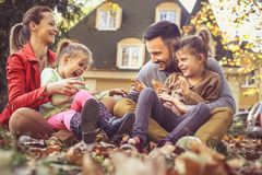 Mutter und Vater, die mit Töchtern draußen spielen lizenzfreies stockbild
