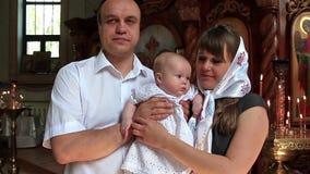 Mutter und Vater mit Baby in der orthodoxen Kirche achtern stock video footage