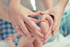 Mutter- und Vatergrifffüße des Babys Stockbilder