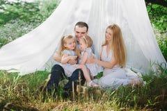 Mutter und Vati, die auf der Natur spielen und zwei Töchter umarmen Stockfoto