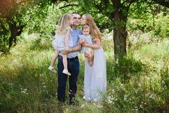 Mutter und Vati, die auf der Natur spielen und zwei Töchter umarmen Stockbilder