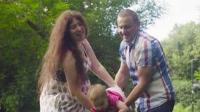 Mutter und Vati, die Baby halten und sie schwingen stock video footage