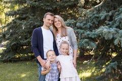 Mutter und Vati, die mit ihrem hübschen Sohn und Tochter spielen - Familie und Kinder draußen im Park - junges schönes Lizenzfreie Stockfotos