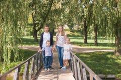 Mutter und Vati, die mit ihrem hübschen Sohn und Tochter spielen - Familie und Kinder draußen im Park - junges schönes Stockbild