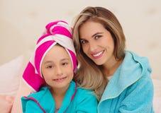 Mutter und wenig Tochtertragen, die blaue Bademäntel im Raum sind lizenzfreies stockfoto
