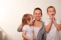 Mutter und zwei blonde Jungen putzen ihre Zähne Lizenzfreie Stockbilder