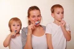 Mutter und zwei blonde Jungen putzen ihre Zähne Stockfotos