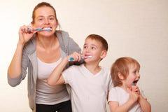 Mutter und zwei blonde Jungen putzen ihre Zähne Stockbilder
