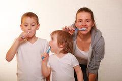 Mutter und zwei blonde Jungen putzen ihre Zähne Lizenzfreies Stockfoto