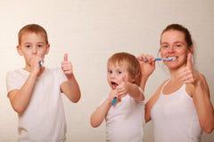 Mutter und zwei blonde Jungen putzen ihre Zähne Stockfoto