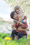 Mutter und zwei Kinder, die Frühlingsgarten bewundern Lizenzfreies Stockbild