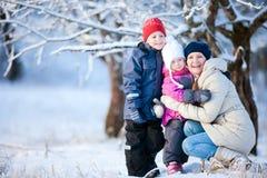 Mutter und zwei Kinder draußen am Winter Lizenzfreies Stockfoto