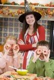 Mutter und zwei Kinder am Halloweenspielen stockbild