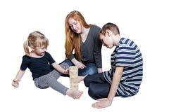 Mutter und zwei Kinder spielen zusammen auf weißem Hintergrund Lizenzfreie Stockfotografie