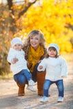 Mutter und zwei kleine Mädchen, die in den Park im Herbst gehen Stockbild