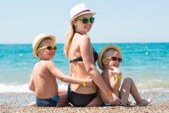 Mutter und zwei Söhne in den Hüten, die auf dem Strand sitzen Sommerfamilienurlaub lizenzfreies stockfoto