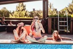 Mutter und zwei Töchter, die das Yoga, im Freien tun stockfotografie