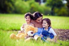 Mutter und zwei Töchter, die im Gras spielen stockfotografie