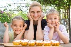 Mutter und zwei Töchter haben kleine Kuchen zugebereitet Lizenzfreie Stockfotos