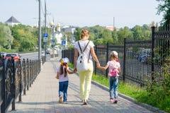 Mutter und zwei Töchter sind auf Bürgersteig entlang der Straße stockfotos