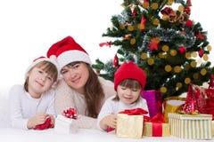 Mutter und zwei Töchter unter Weihnachtsbaum Lizenzfreies Stockfoto