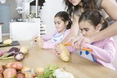 Mutter und Zwillinge, die Kartoffeln in der Küche abziehen lizenzfreie stockbilder