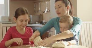 Mutter-unterrichtende Tochter wie zum Koch und zu Kindern, die Mutter-knetendem Teig helfen, um Plätzchen zu backen stock video footage