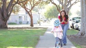 Mutter-unterrichtende Tochter, zum des Rollers zu reiten stock video