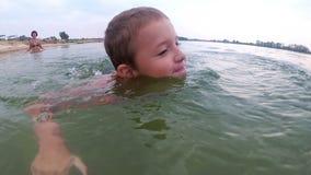 Mutter unterrichtet das Kind, im Fluss zu schwimmen stock video