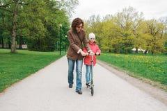 Mutter unterrichtet ihr Kind, einen Roller zu reiten Stockfotografie