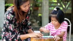 Mutter unterrichtet ihr Tochterspielspiel stock footage
