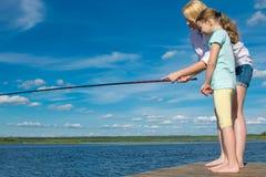 Mutter unterrichtet ihre Tochter, auf dem Pier draußen stehen, gegen den blauen Himmel zu fischen stockfotografie