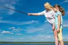 Mutter unterrichtet ihre Tochter, auf dem Pier, gegen den blauen Himmel zu fischen lizenzfreie stockfotografie