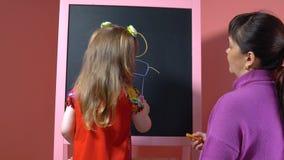Mutter unterrichtet ihre Tochter, mit Kreide zu zeichnen stock video