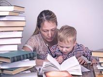 Mutter unterrichtet Sohn, unter den Stapeln von Büchern zu lesen Lizenzfreie Stockbilder