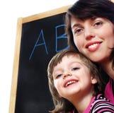 Mutter unterrichtet Tochter zu lesen lizenzfreies stockfoto