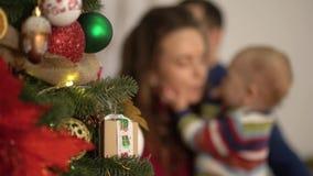 Mutter, Vater und kleines Baby, die Baumnahaufnahme des neuen Jahres verzieren Frauenholdingkind nahe Tannenbaum, Darstellen hell stock footage